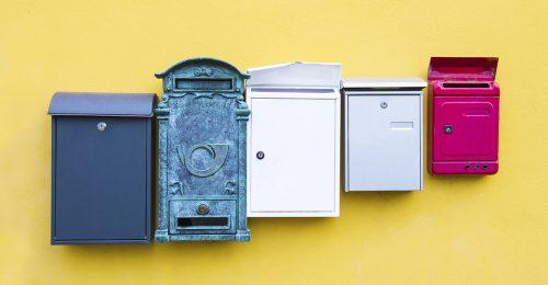 Gekleurde brievenbussen tegen gele wand